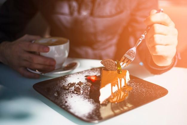 Close-up, de, mão homem, segurando, garfo, em, a, fatia bolo