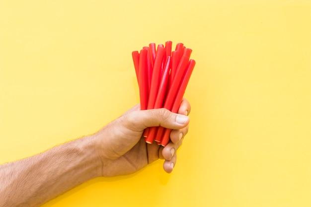 Close-up, de, mão homem, segurando, vermelho, alcaçuz, bala doce, contra, fundo amarelo