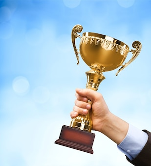 Close-up de mão humana segurando o troféu dourado em fundo azul desfocado