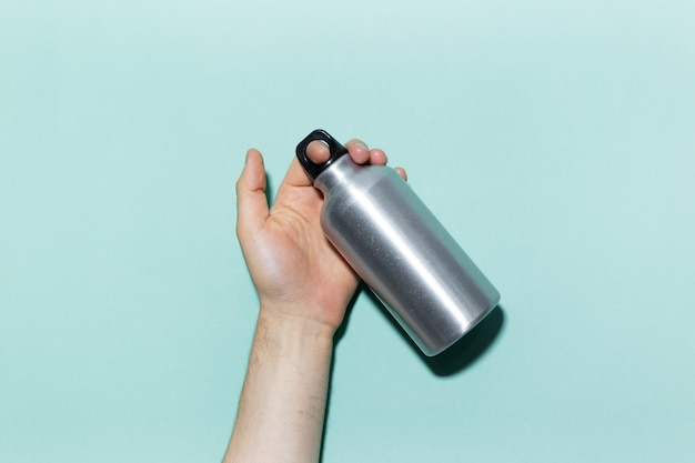 Close-up de mão masculina segurando eco, garrafa de água térmica de alumínio reutilizável em fundo de estúdio de ciano, cor aqua menthe.