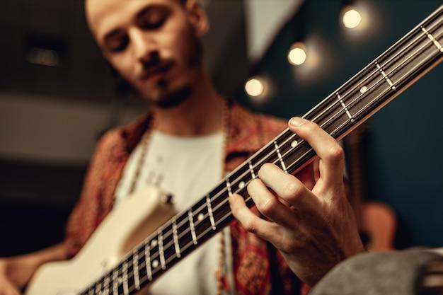 Close-up de mão masculina tocando guitarra elétrica no escuro