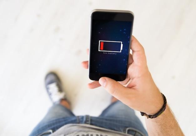 Close-up de mão masculina usando telefone inteligente com bateria fraca