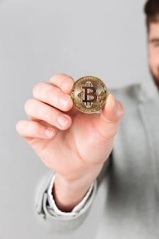 Close-up de mão masculino mostrando bitcoin dourado