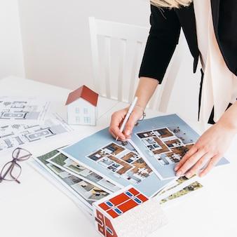 Close-up, de, mão mulher, caneta segurando, trabalhando, ligado, blueprint, em, escritório