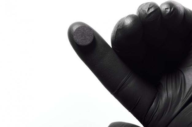 Close-up de mão na luva de látex preta segurando o comprimido preto.