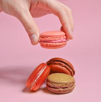Close-up de mão segurando biscoitos coloridos