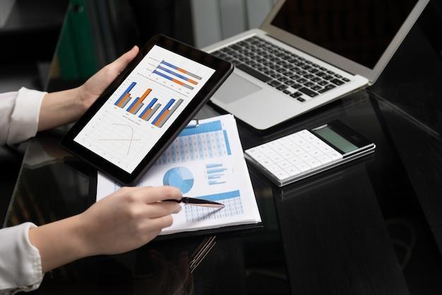 Close-up de mão segurando o tablet e caneta no gráfico