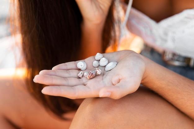 Close-up de mão segurando pequenas conchas
