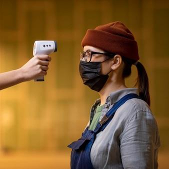 Close-up de mão segurando termômetro para mulher