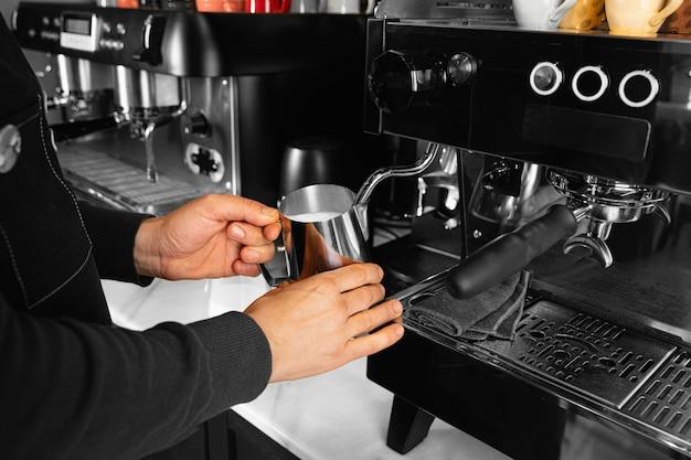 Close-up de mão segurando um copo com leite