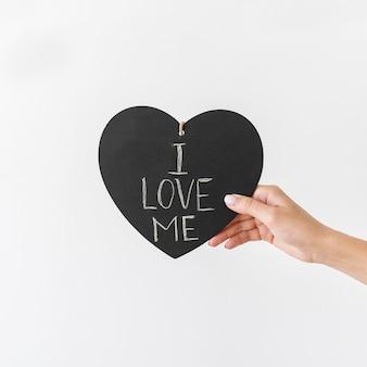 Close-up de mão segurando um coração com texto