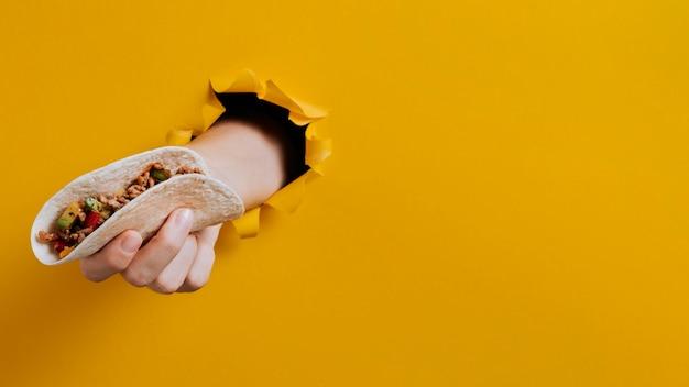 Close-up de mão segurando um taco com cópia-espaço