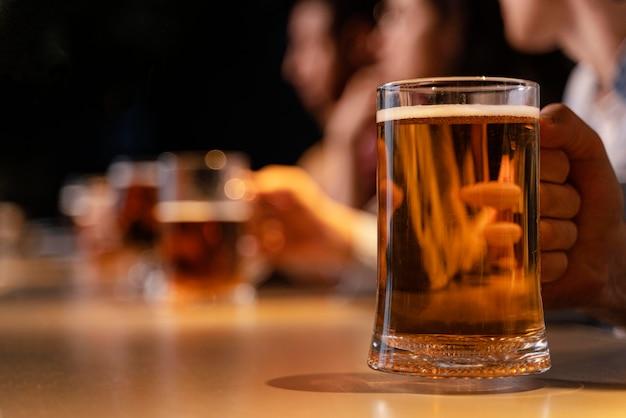 Close-up de mão segurando uma caneca de cerveja