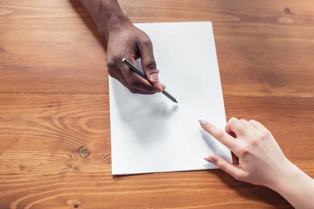 Close-up de mãos afro-americanas masculinas e brancas, trabalhando no escritório