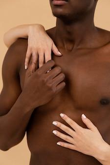 Close-up de mãos brancas segurando um homem negro