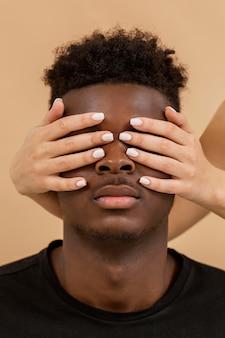 Close-up de mãos cobrindo os olhos do homem