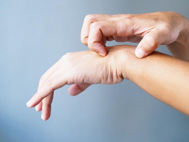 Close-up de mãos coçando nos braços de coceira de doenças de pele, isoladas na parede cinza