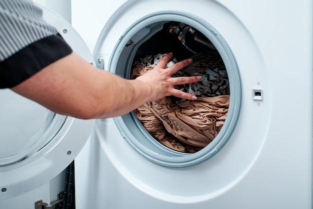 Close-up de mãos colocando roupas na máquina de lavar
