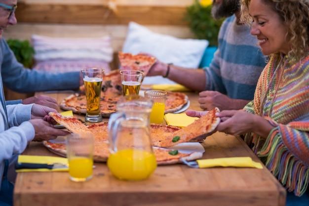 Close-up de mãos com copo com cerveja e suco de laranja tilintando no centro da mesa - duas grandes pizzas na mesa de madeira
