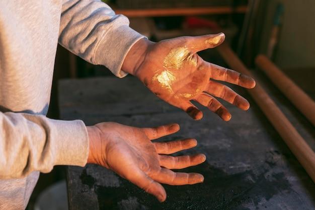 Close-up de mãos com glitter dourado