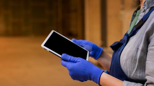 Close-up de mãos com luvas segurando o tablet
