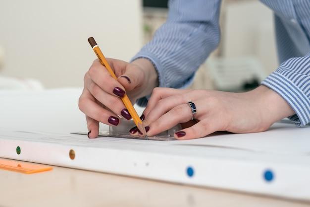 Close-up de mãos com um lápis e régua, desenhe em um papel branco