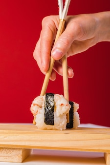 Close-up de mãos comendo sushi com pauzinhos.