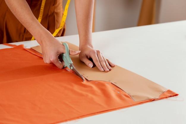 Close-up de mãos cortando tecido