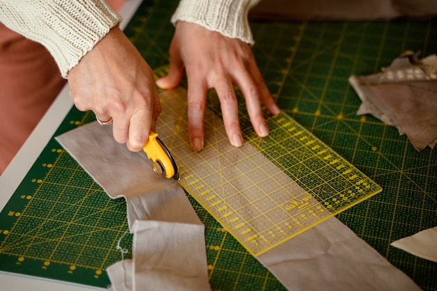 Close-up de mãos de alfaiate trabalhando com agulhas
