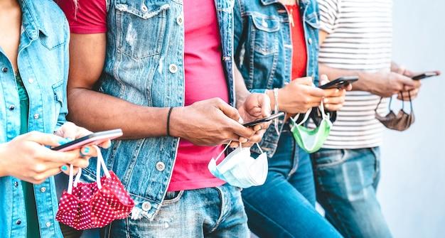 Close-up de mãos de amigos com máscaras usando o aplicativo de rastreamento em telefones móveis inteligentes