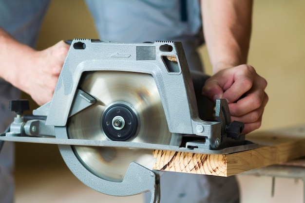 Close-up de mãos de carpinteiro muscular usando nova serra elétrica circular poderosa poderosa moderna brilhante para cortar tábua de madeira dura