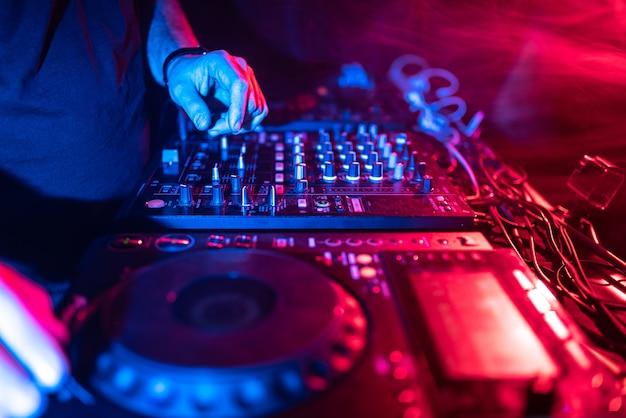Close-up de mãos de dj, controlando a mesa de música em uma boate