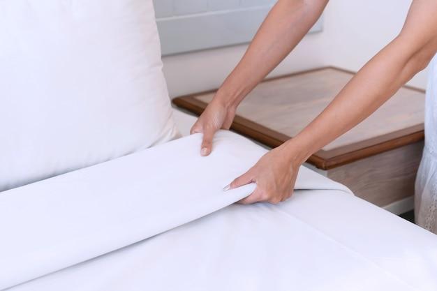 Close-up de mãos de mulher asiática configurando lençol branco em quarto de hotel