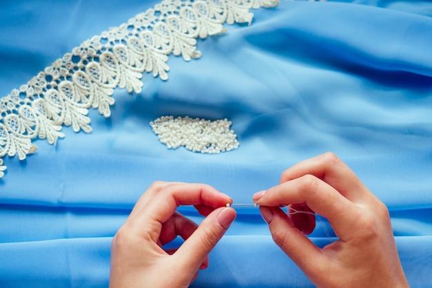 Close-up de mãos de mulher costureira alfaiate (costureira), estilista, vestido de chiffon azul costura miçangas em renda sobre um fundo azul no estúdio