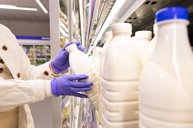 Close-up de mãos de mulher em luvas médicas escolhe produtos lácteos, abrindo a geladeira no supermercado