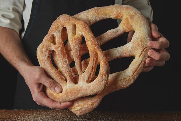 Close-up de mãos de padeiro com pão fougas
