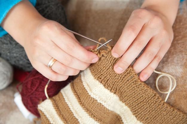 Close up de mãos de tricô da mulher