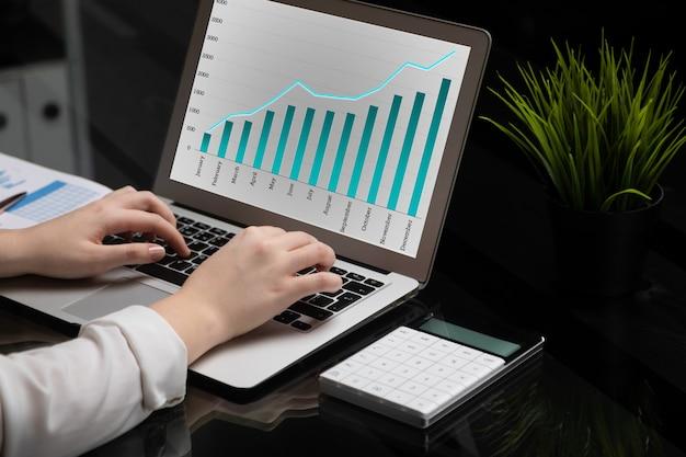 Close-up de mãos digitando no laptop com tela preta em branco ao lado de gráficos e calculadora