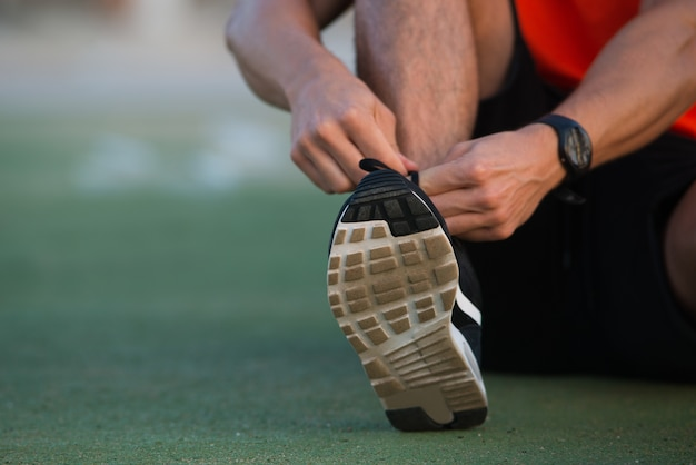 Close-up de mãos do sexo masculino amarrando sapatos esportivos