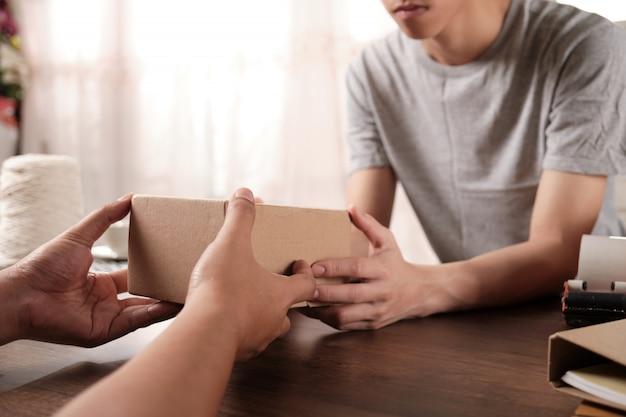 Close-up de mãos está segurando a caixa de papelão para entregar ao cliente.