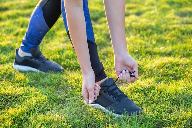 Close-up de mãos femininas, amarrando o cadarço no tênis antes do treino. corredor se preparando para o treinamento. conceito de estilo de vida ativo do esporte.