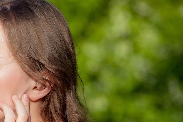 Close-up de mãos femininas colocando aparelho auditivo no ouvido. aparelho auditivo digital moderno para surdez e pacientes com deficiência auditiva