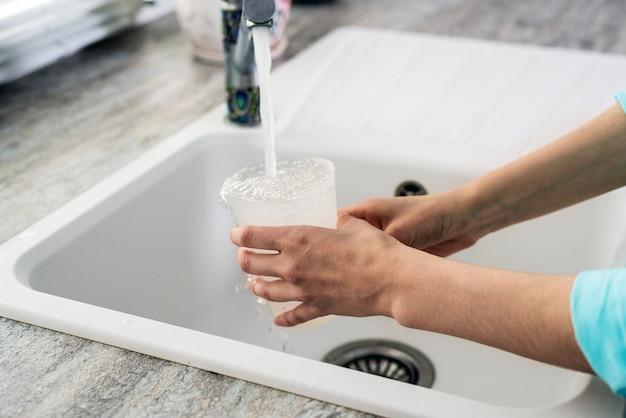 Close-up de mãos femininas com copo plástico ganhando água da torneira na pia da cozinha