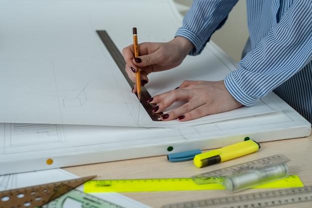 Close-up de mãos femininas com um lápis e régua desenhar uma imagem
