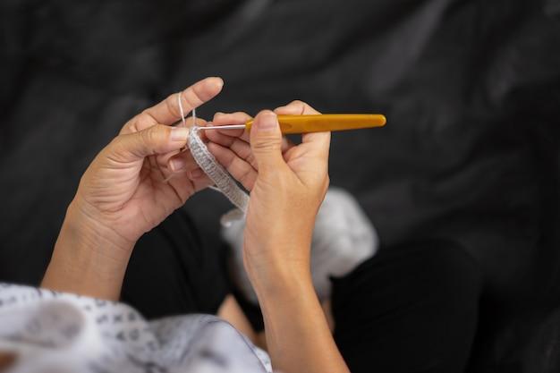 Close-up de mãos femininas de tricô, gancho de tricô feminino, vista de cima