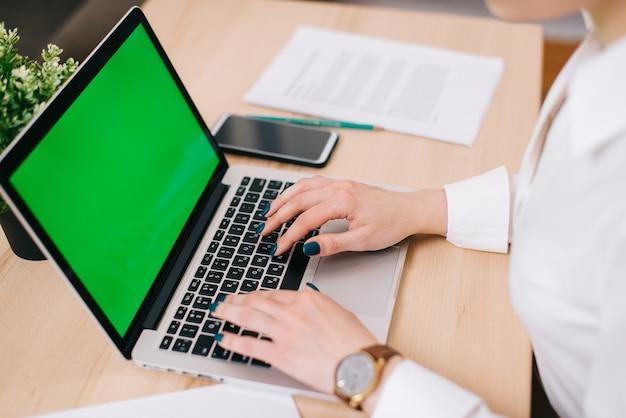 Close-up de mãos femininas, digitando o texto no teclado do laptop