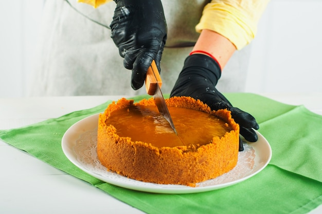 Close-up de mãos femininas em luvas cortando cheesecake de caramelo