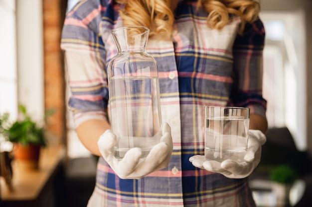 Close-up de mãos femininas em luvas segurando uma garrafa e um copo com água pura