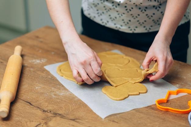 Close up de mãos femininas fazendo biscoitos de massa fresca em casa