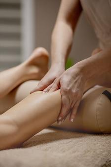 Close-up de mãos femininas fazendo massagem nos pés. mulher apreciando a massagem nos pés de reflexologia em spa de bem-estar.